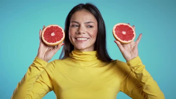 Thumbnail for Portrait of young beautiful woman with two half of juicy grapefruit on blue studio background