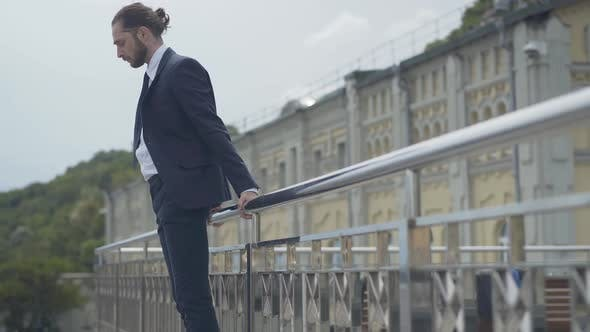 Thumbnail for Side View Wide Shot of Desperate Caucasian Businessman in Suit Standing at Bridge Edge Attempting To