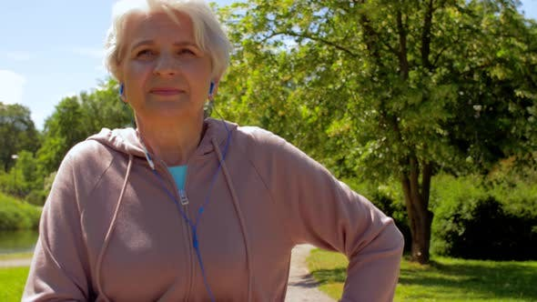 Cover Image for Senior Woman with Earphones Running in Summer Park