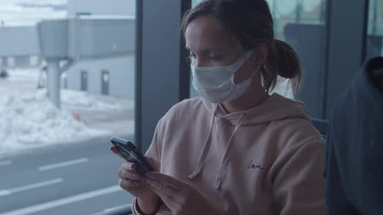 Woman in Protective Mask Uses Phone Waiting for Flight