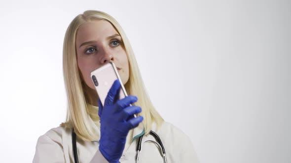 Female Nurse Uses Smartphone During Break