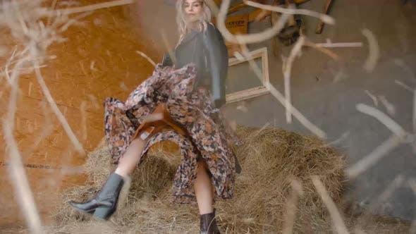 Woman Kicking Hay in Barn