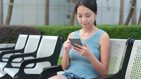 Cover Image for Young Woman use of mobile phone in the park