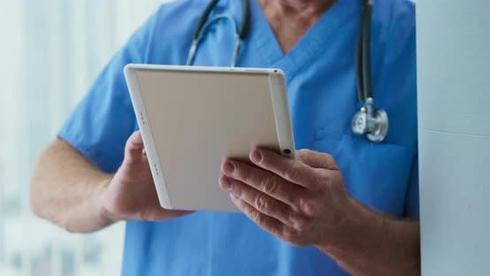 Thumbnail for Close up on hands of doctor reading patient notes in hospital on tablet computer