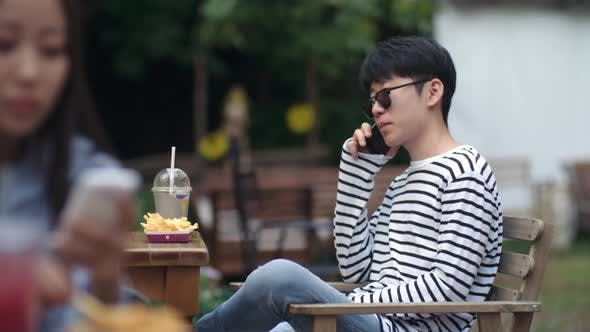 Cover Image for Young Asian Man Speaking on Cell Phone at Lunch in Outdoor Cafe