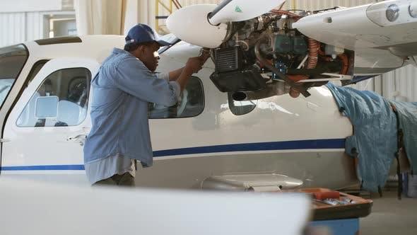 Thumbnail for Man Repairing Propeller Engine on Airplane