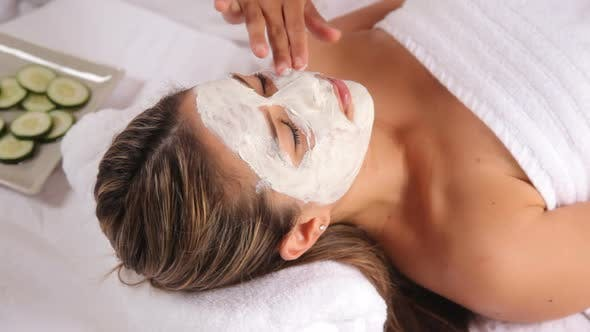Woman at spa with facial mask and cucumbers
