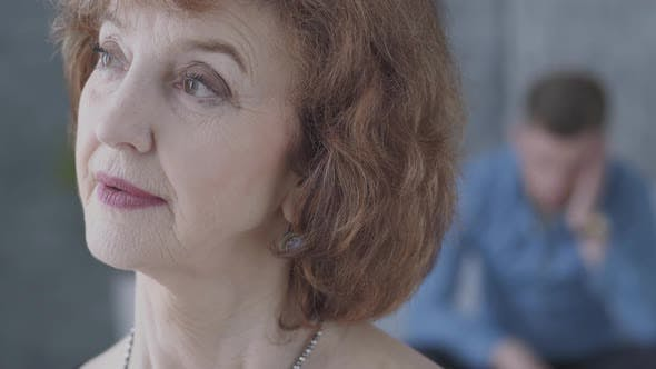 Thumbnail for Close Up Portrait of Cute Mature Woman Looking Away in the Foreground. The Blurred Figure of the Man