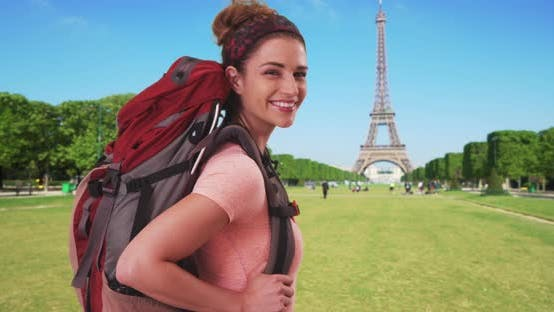 Thumbnail for Happy Caucasian woman standing near Eiffel Tower with backpack on