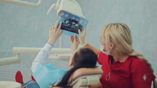 Girl Patient Shows on an Xray Picture What Teeth Should Be Treated with a Dental Clinic