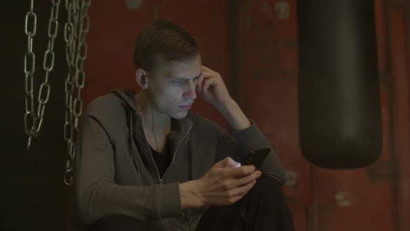 Handsome Man Choosing Audio Application on Phone
