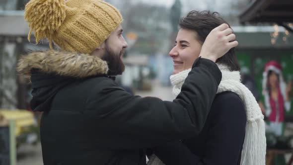 Cover Image for Side View of Young Caucasian Man in Love Touching Girlfriend's Hair and Talking. Happy Couple