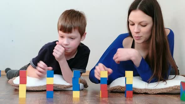 Thumbnail for Building a Small and Big Towers From Blocks and Cubes. Mom and Son Playing Together
