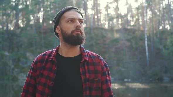 Young Bearded Man with an Axe Walk in Forest. Unshaven Forester with an Ax Outdoors