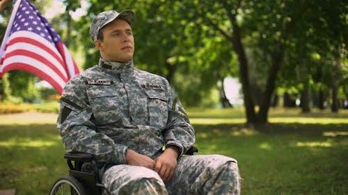 Veteran Saluting, Sitting in Wheelchair, Waving Flag Behind, Independence Day