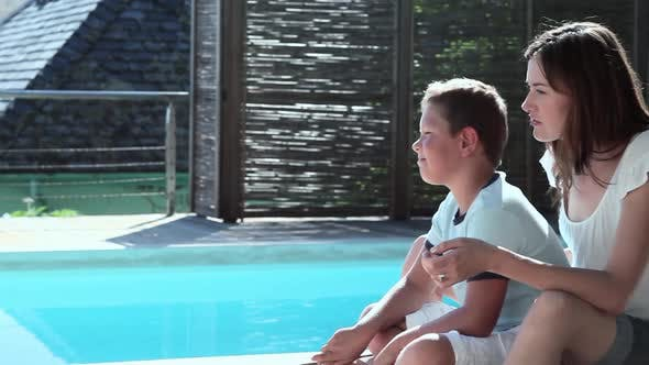 Thumbnail for Mother and son hugging on lounger by pool