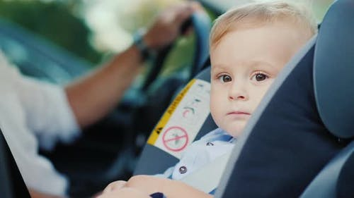 Portrait of a Cute Little Boy Boy, Sits in a Children's Car Seat Near the Pope. Safety and Child