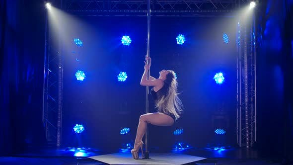 Thumbnail for Exotic Pole Dance. Attractive Girl Performs Tricks on a Pole in a Dark Studio with Blue Neon Lights