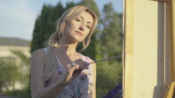 Thumbnail for Porträt der schönen blonden kaukasischen Frau Malerei Bild im Freien. Charmante Künstlerin