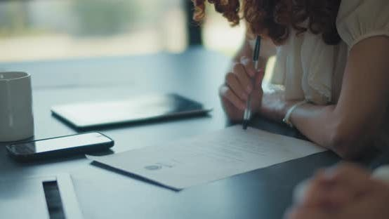 Thumbnail for Close up of a businesswoman signing a contract during a business meeting. Slow motion