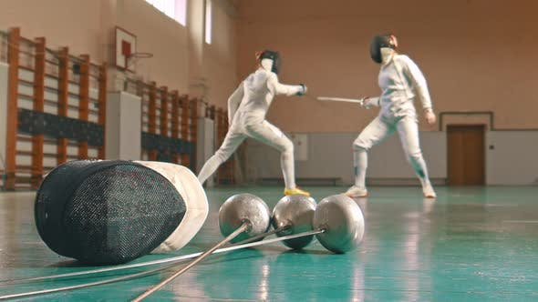 Thumbnail for Two Young Women Fencers Having a Training in the School Gym - Gear on the Foreground
