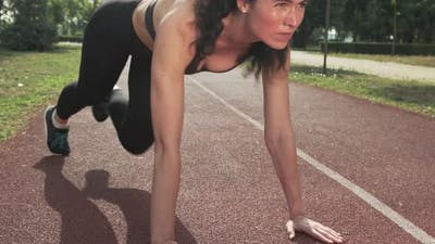 Young Woman Does Running Plank on Track Stadium Outdoors