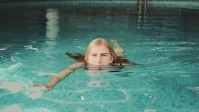 Close Up of Blonde Woman Swimming to the Camera