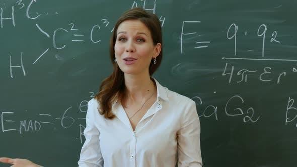 Thumbnail for Junge Attraktive weibliche Lehrerin der Mathematik interagieren mit Ihren jungen Grundschülern fragen