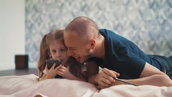 Cute Little Girl and Daddy Do Homework Online with Phone