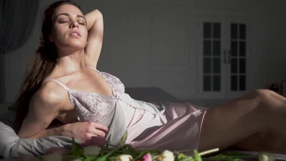 Cover Image for Beautiful Girl in a Nightgown Lying on a Bed with Tulips and Enjoying Her Body, Touching Her Long