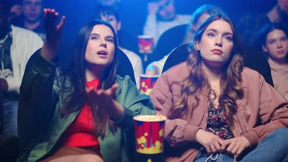 Thumbnail for Frustrated Women Gesticulating in Cinema. Upset Girls Watching Film Indoor.