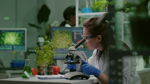 Pharmaceutical Scientist Looking at Green Leaf Sample on Microscope