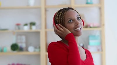Young African American Woman is Listening to Music and Dancing in Apartment Room Spbi