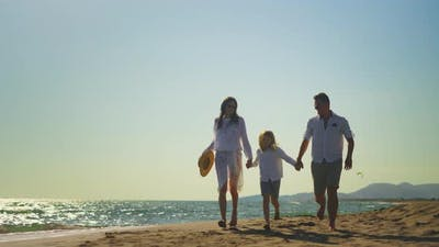 Parents with son running on beach