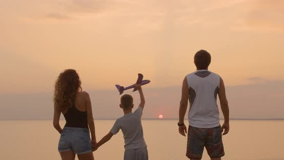 Thumbnail for A Happy Family. The Boy with His Father and Mother with Toy Airplane at the Sunset