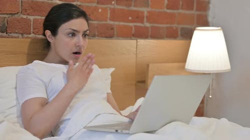 Young Indian Woman Reacting to Loss on Laptop in Bed