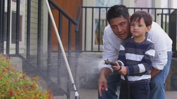 Thumbnail for Father and son watering plants in yard