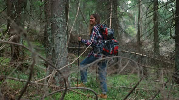 Woman with Backpack Trekking in Woods