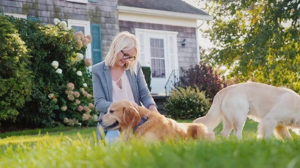 Thumbnail for Woman Playing with Two Gold Retrievers in Her Yard Near the House