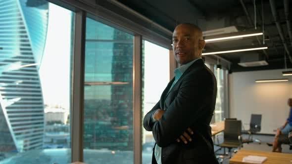 Aframerican Businessman Near Modern Office Windows Smiles.
