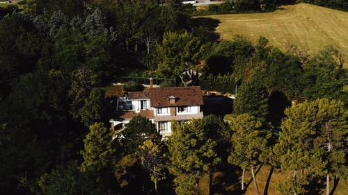 Drone Zooming Out Above Beautiful House Mansion in Italy Surrounded By Green Trees and Hilly Fields