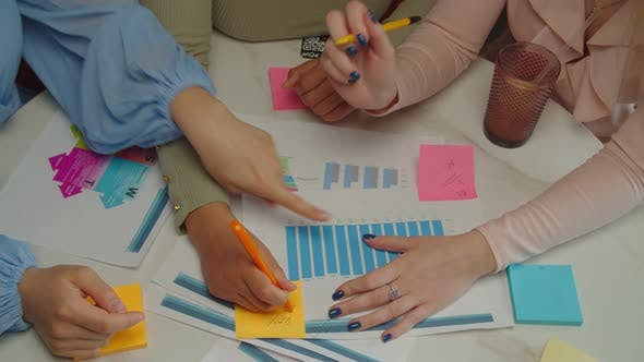 Diverse Female Hands Writing Ideas on Sticky Notes