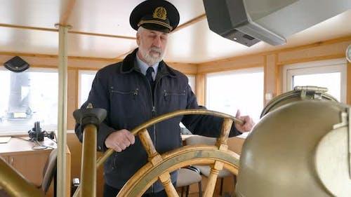 Portrait Captain of Ship Holding Steering Wheel on Captain Bridge. Bearded Sailor Turning Helm