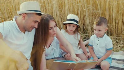 Mother Reading Book to Children at Picnic