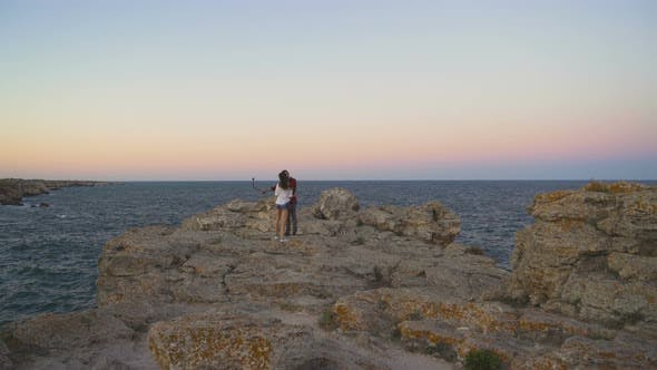 Thumbnail for Happy Couple Walking on Rocky Shore at Sunset with Sea Horizon in the Background