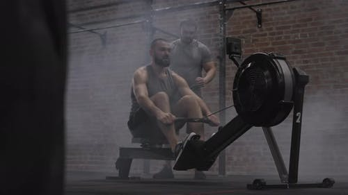 Sportler trainiert auf Trainingsgerät im Fitnessstudio
