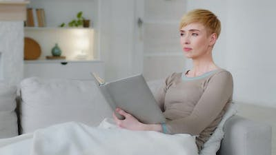 Dreamy Woman Relaxing Holding Book Reading Sit on Sofa Thinks Over Read Reflects Looking Into