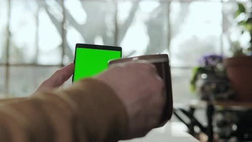 A Male Hand Holds a Phone with a Mockup Green Screen and Drinks Coffee
