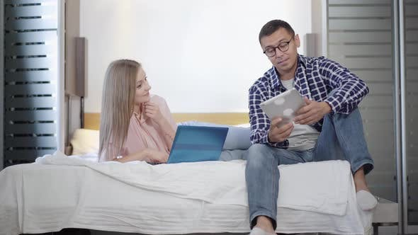 Thumbnail for Wide Shot Portrait of Cheerful Young Couple Surfing Internet in Bedroom on Weekend
