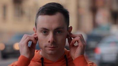 Man Puts on Earphones on the Street